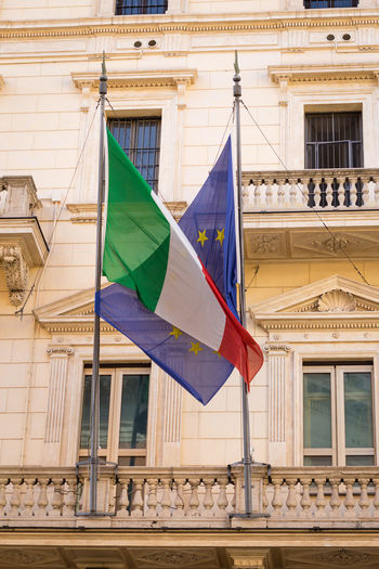 Flag of Italy and Europe connected to each other in front of government building in Rome, Italy Rome Roma Flag Flags Banner Europe European  European Union Brussels Crises Embrace Connection Friendship Politics And Government Metaphor Government Government Building