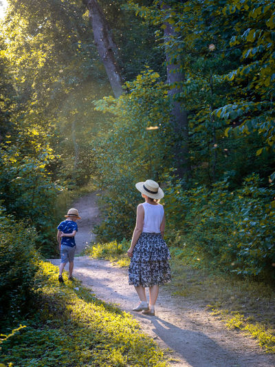 Mother And Son Evening Light Adult Casual Clothing Clothing Couple - Relationship Day Emotion Forest Full Length Growth Hat Leisure Activity Lifestyles Nature Outdoors People Positive Emotion Rear View Togetherness Two People Walking Women Summer Road Tripping