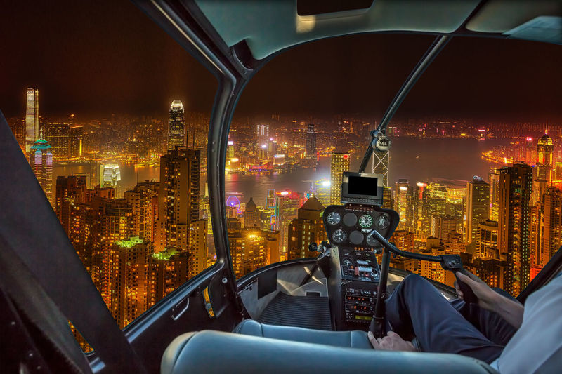 Illuminated Cityscape Against Sky At Night Seen Through Helicopter