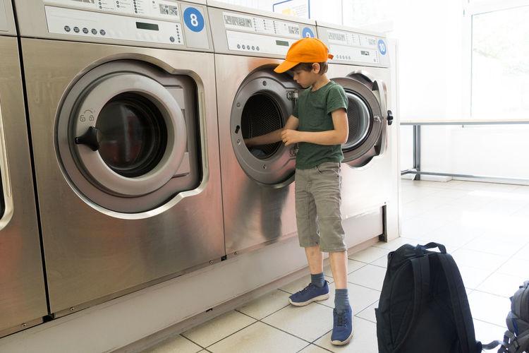 Boy using washing machine in room