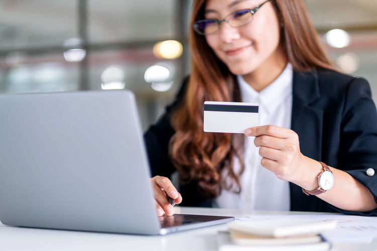 Mid adult woman using laptop while holding credit card over table