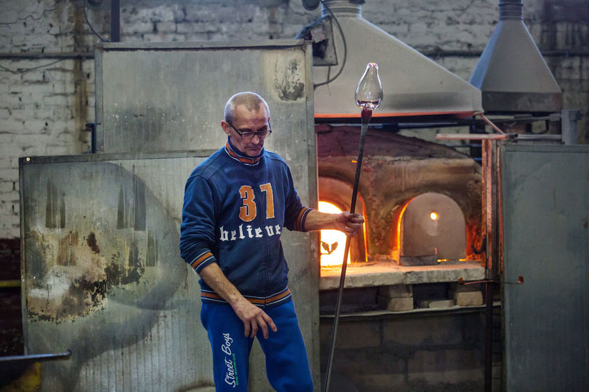 Adult Day Factory Glass - Material Glass Factory Indoors  Industry Manual Worker Manufacturing Occupation Men Metal Industry Muranoglass Occupation Occupational Safety And Health One Person People Protective Workwear Real People Standing Steel Worker Three Quarter Length Welder Working Workshop