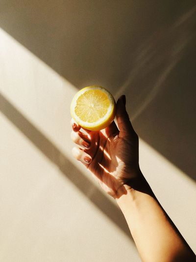 Cropped hand of woman holding lemon
