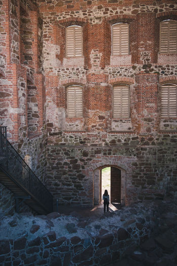 Rear View Of Woman Walking Towards Door