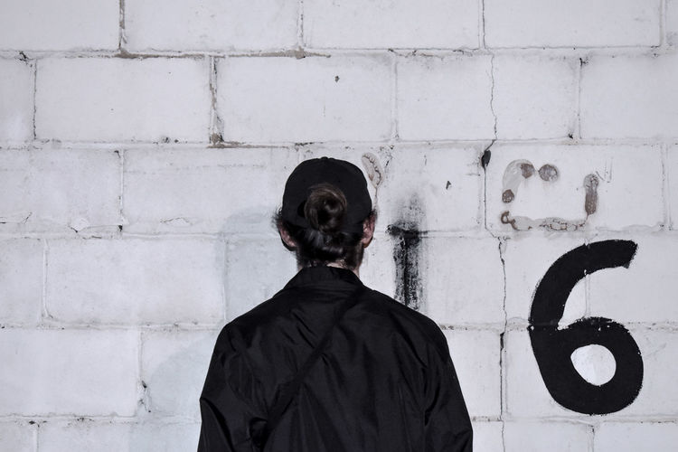 Rear view of man with hair bun standing by white wall