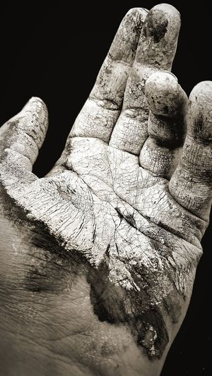 Close-up of hand on mud against black background