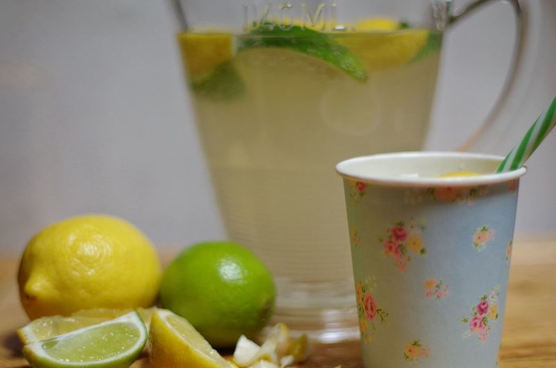 Close-up of disposable cups with fresh lemonade in glass jug against wall