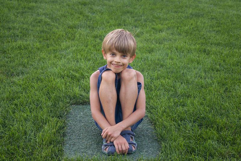 Portrait of boy sitting on stone amidst grass