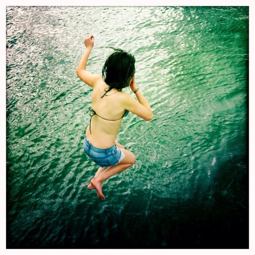 High angle view of young woman jumping into sea