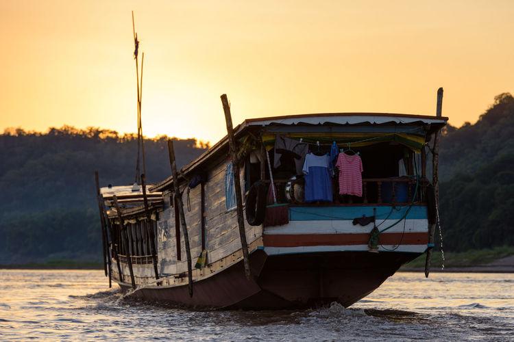 Passenger craft sailing in mekong river during sunset