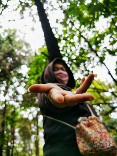 Low angle view of woman wearing mask standing in forest