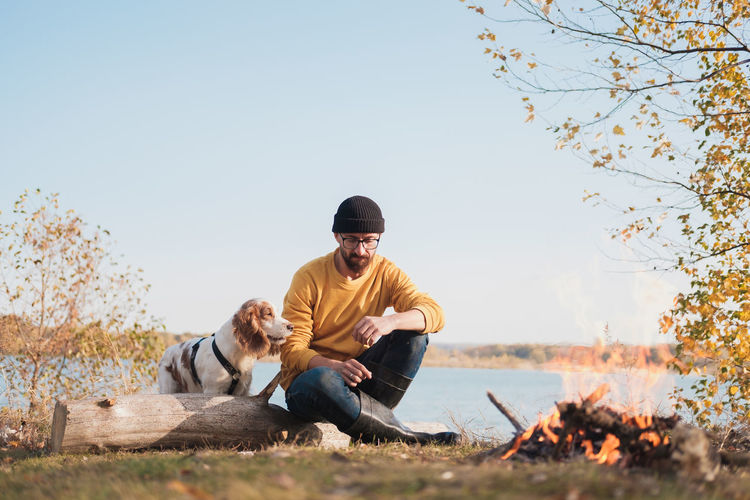 Man with dog sitting against sky