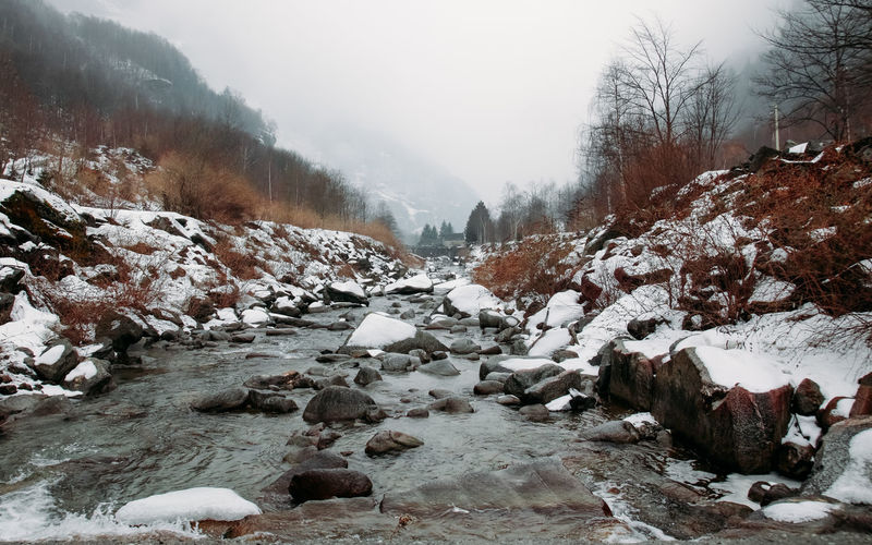 Flowing Water Loneliness Riverside Beauty In Nature Cold Days Cold Temperature Environment Flowing Water Fog Landscape Mountain Nature No People Non-urban Scene River Riverscape Scenics - Nature Snow Snow And Water Snowcapped Mountain Torrential Rain Tranquil Scene Tranquility Tree Winter
