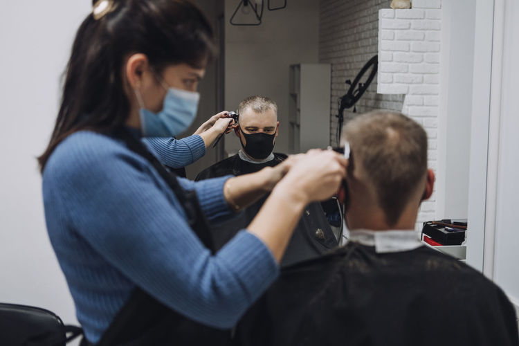 Female barber cutting hair of customer in saloon