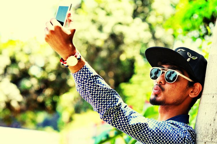 Young man taking selfie with mobile phone
