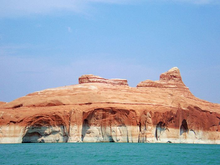 Scenic view of lake powell and rock formations against clear blue sky