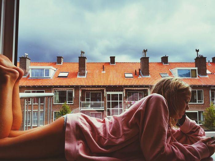 Woman sitting by buildings against sky