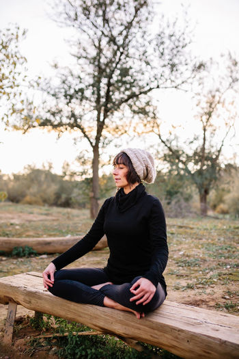 Smiling woman wearing knit hat meditating on bench at park