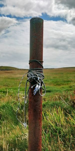 Rusty chain on field against sky