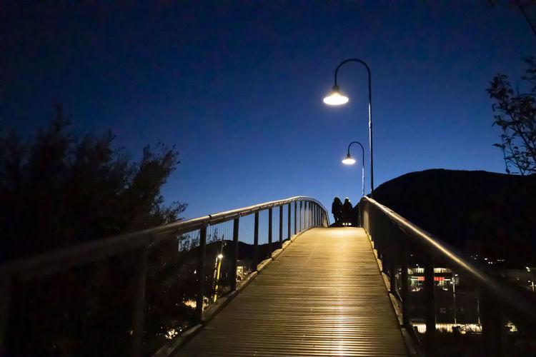 Narrow footbridge along street lights at night