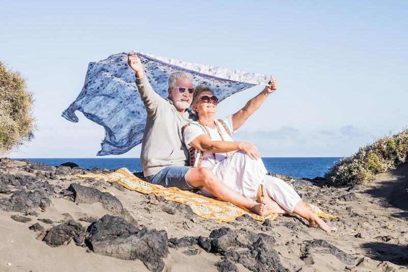 Couple sitting on beach against sky