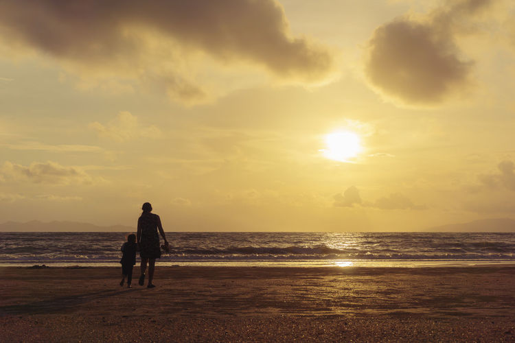 Rear view of silhouette mother and daughter walking at beach against sky during sunset