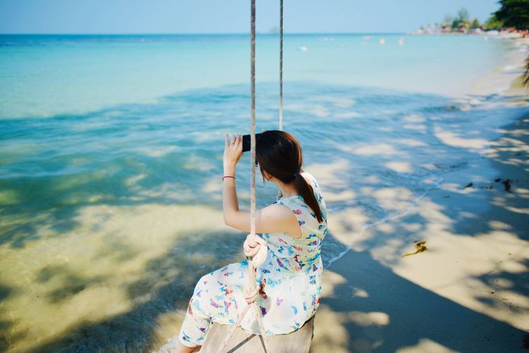 High angle view of woman photographing sea while sitting on swing at beach