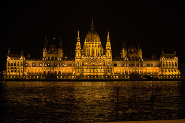 Illuminated hungarian parliament building by river in city at night