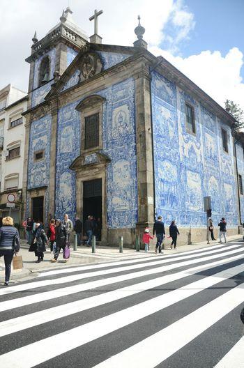 Group of people walking on road against buildings