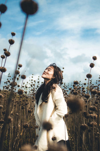 Young woman looking at camera against sky