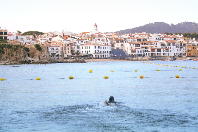 Woman swimming in sea against buildings