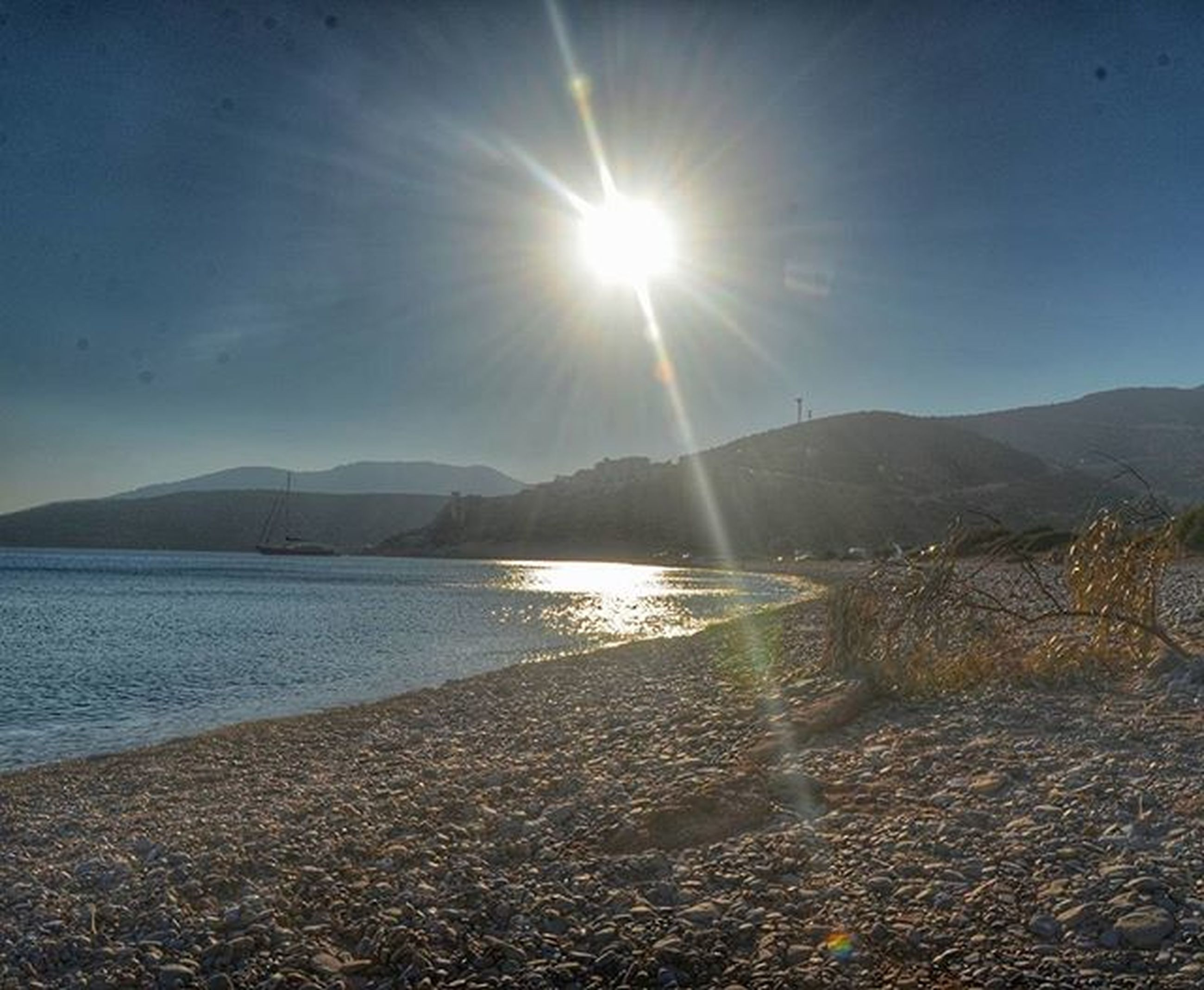 water, mountain, tranquil scene, tranquility, sun, scenics, beauty in nature, sunlight, sunbeam, nature, sky, reflection, sea, lens flare, mountain range, beach, lake, clear sky, idyllic, shore