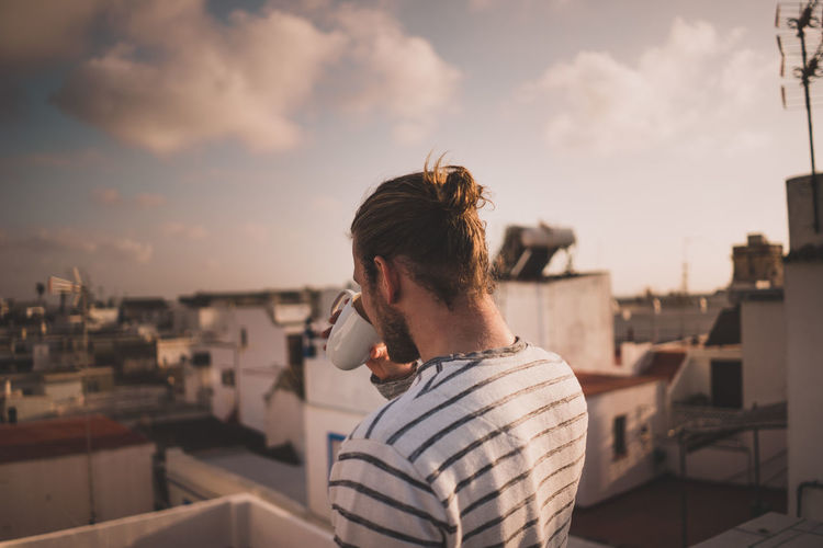 Man drinking coffee over roof tops Coffee Holidays Morning Travel Architecture Building Exterior Built Structure Casual Clothing Day Focus On Foreground Leisure Activity Nature Nautical Vessel One Person Outdoors Real People Rear View Sea Sky Standing Striped Vacation Warm Water Young Adult