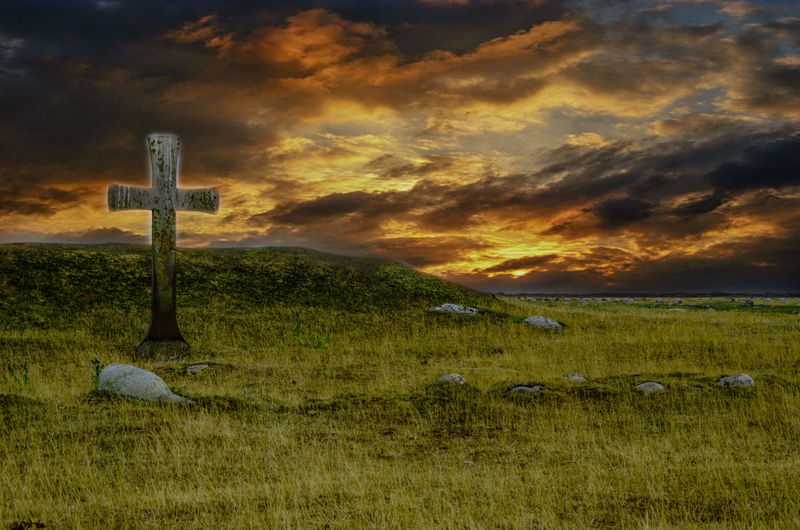 Cross on field against sky during sunset