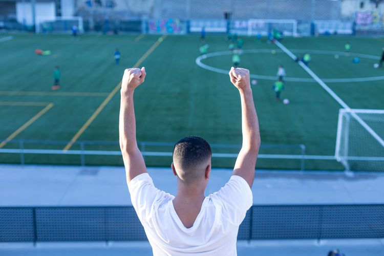 Rear view of man with arms raised against blurred background