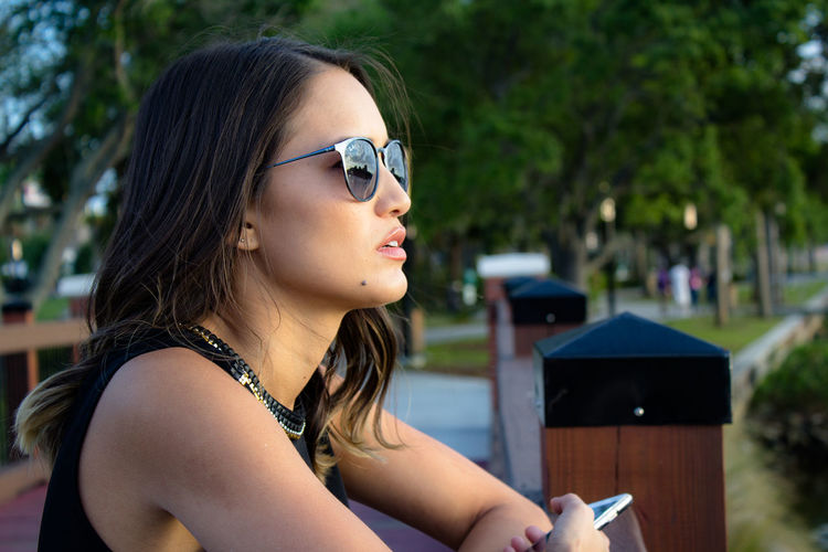 Side View Of Young Woman In Sunglasses Standing At Park
