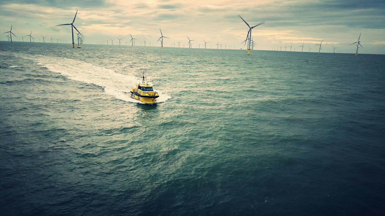 Ferry Crossing The Sea With Industrial Windmills In The Background