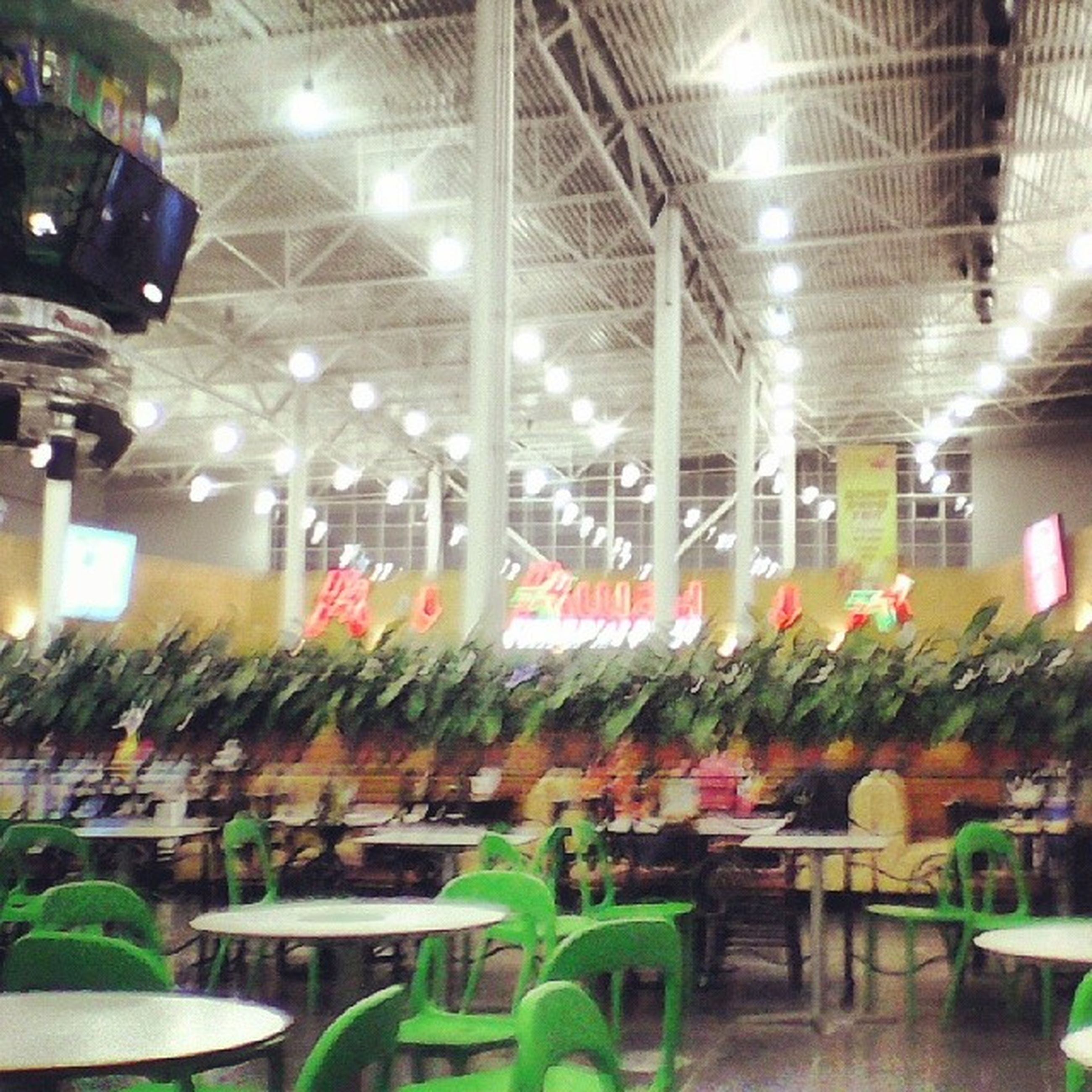 indoors, illuminated, incidental people, lighting equipment, glass - material, night, restaurant, arrangement, reflection, decoration, table, for sale, variation, large group of objects, chair, freshness, retail, potted plant, abundance, ceiling