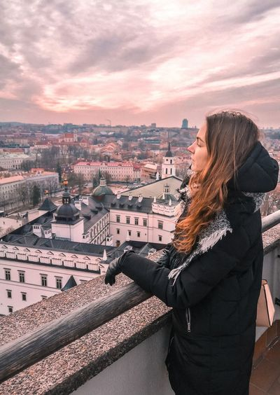 Side view of woman looking at cityscape against sky during sunset