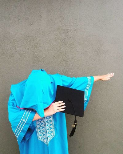 Grad Dab Graduation Adult Blue Body Part Casual Clothing Clothing Convocation Day Gesturing Holding Human Body Part Jeans Leisure Activity Lifestyles Obscured Face One Person Outdoors Real People Standing Three Quarter Length Wall - Building Feature Women