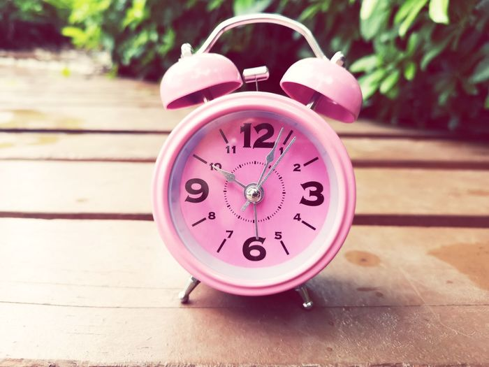 Pink clock on wooden EyeEm Selects Clock Face Minute Hand Clock Hour Hand Time Urgency Alarm Clock Single Object Still Life Close-up Ringing Bell Number 12 Deadline 12 O'clock Hourglass Checking The Time Instrument Of Time Stopwatch Countdown Beat The Clock Timer Waking Up