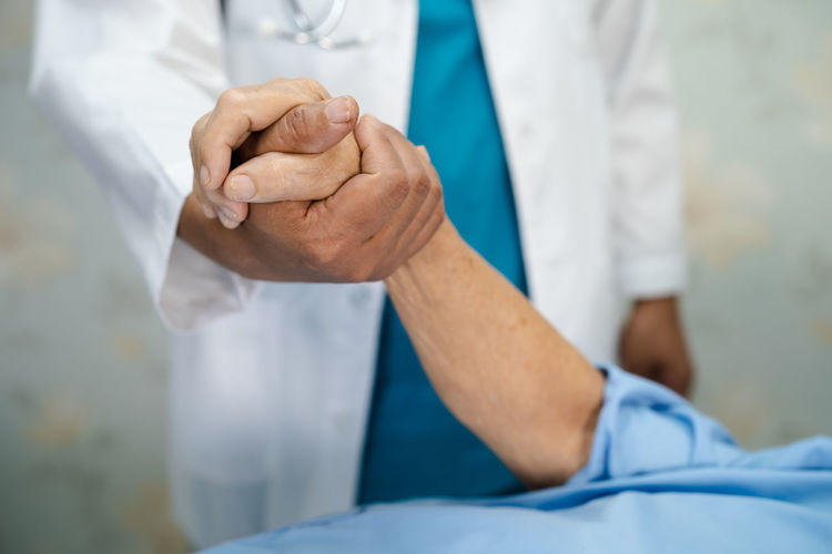 Midsection of doctor consoling patient at hospital