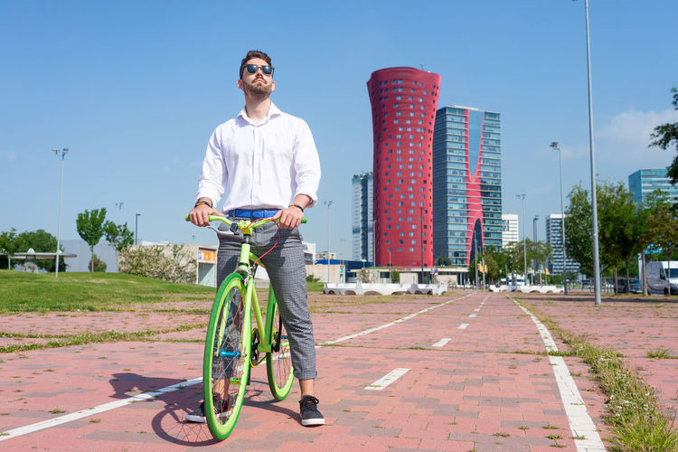 Young man riding bicycle against sky
