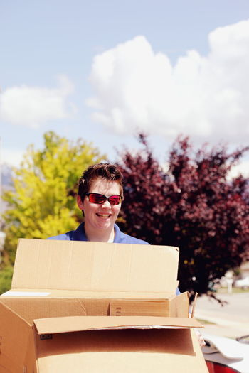Smiling mid adult lesbian woman carrying cardboard box