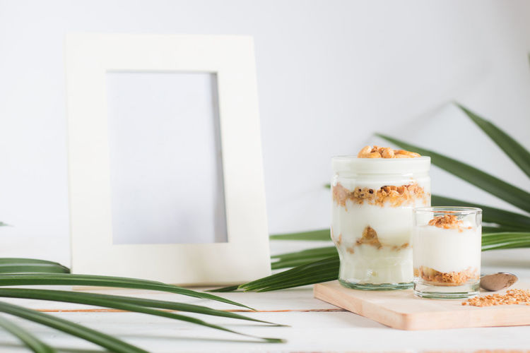 Close-up of dessert in glass by empty picture frame on table