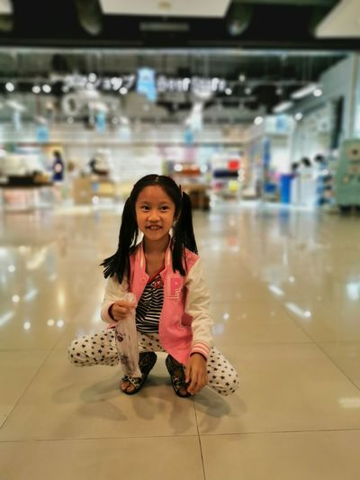Smiling girl crouching on tiled floor in shopping mall