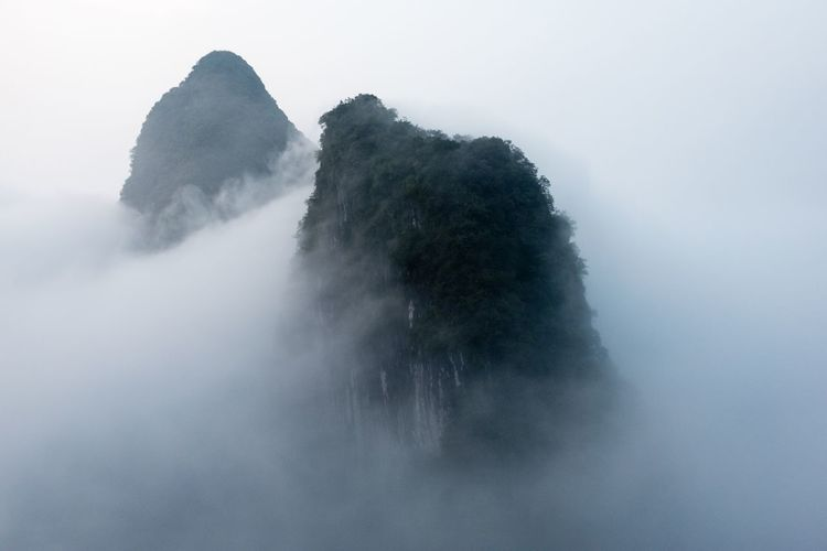 Scenic view of foggy weather against sky
