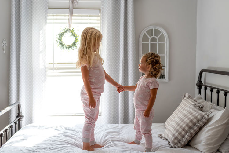 Full length of mother and girl on bed at home