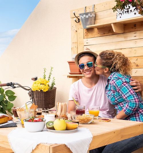 Portrait of boy been kissed by mother during breakfast at building terrace