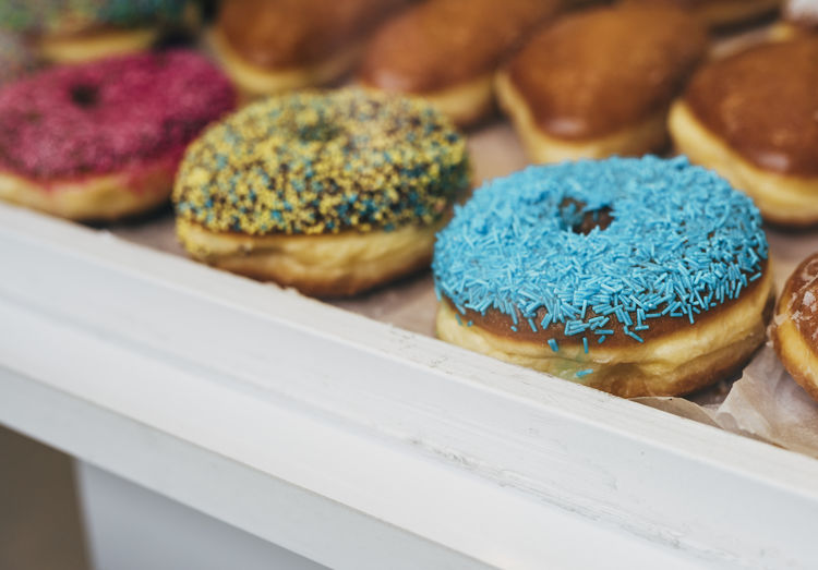 pastries with sugar sprinkles in different colors Food And Drink Food Freshness Indulgence Baked Sweet Food Close-up Indoors  Sweet Temptation No People Dessert Ready-to-eat Unhealthy Eating Still Life Selective Focus Choice Variation Cake Tray Snack Bagel Sugar Sprinkles Pastries Variety